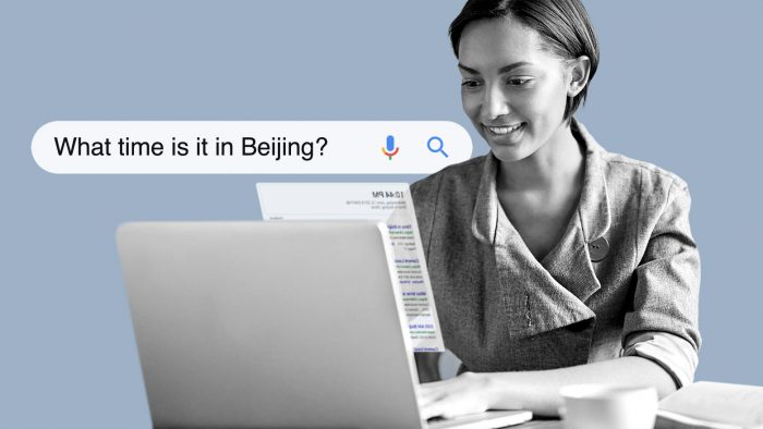 """Person, die auf einem Laptop die Suchanfrage """"Wie spät ist es in Peking"""" eingibt."""