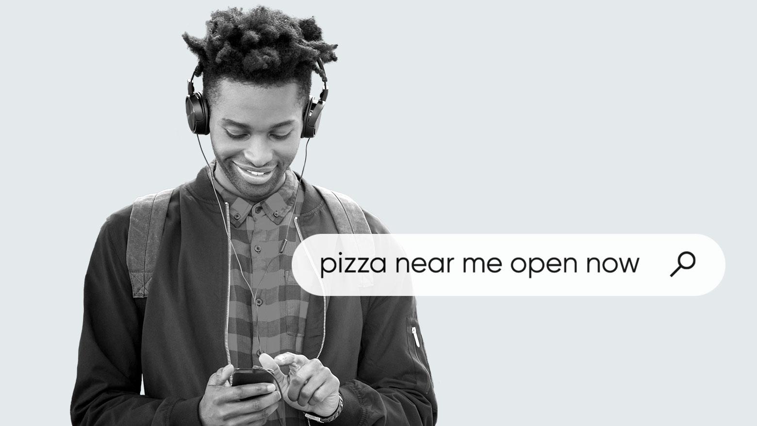 """Mann mit Kopfhörern nutzt sein Handy zur Suche nach """"Pizza in meiner Nähe jetzt geöffnet"""""""
